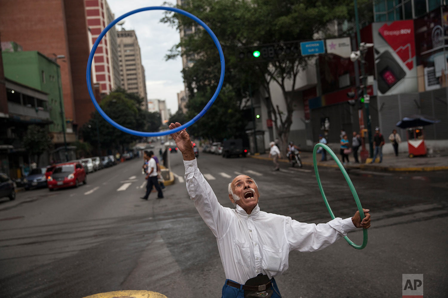 """Jose Bestilleiro, 83, from Spain, performs for tips at an street intersection in downtown Caracas, Venezuela, Sunday, Oct. 29, 2017. Bestilleiro said he's been performing every day for the past 15 years, and brings in at least 5,000 Bolivars a day, which on the black market is 11 cents and is the price of a cheap """"arepa"""" sandwich. (AP Photo/Rodrigo Abd)"""