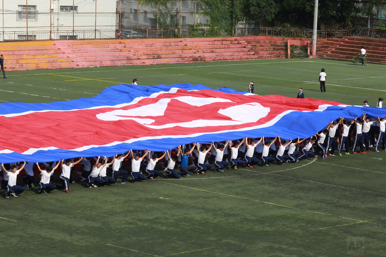 In this Sept. 26, 2017, photo, a student flag team practices a performance waving red, white and blue banners to form th North Korea national flag at a Tokyo Korean high school in Tokyo. (AP Photo/Eugene Hoshiko)