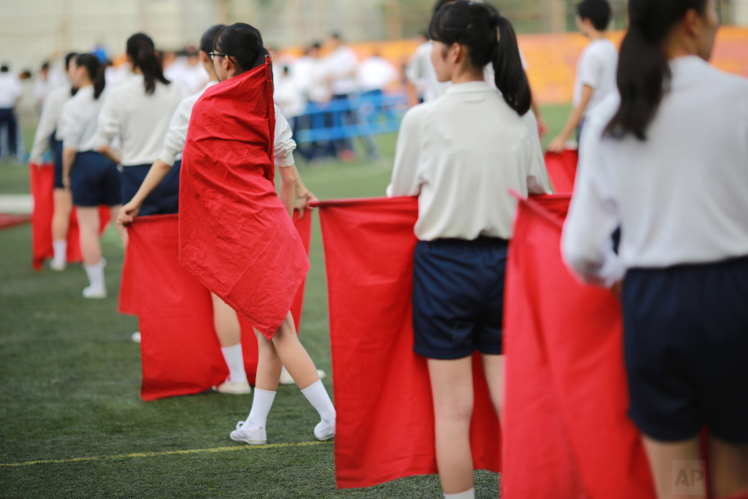 In this Sept. 26, 2017, photo, students practice flag cheering routines at a Korean high school in Tokyo. (AP Photo/Eugene Hoshiko)