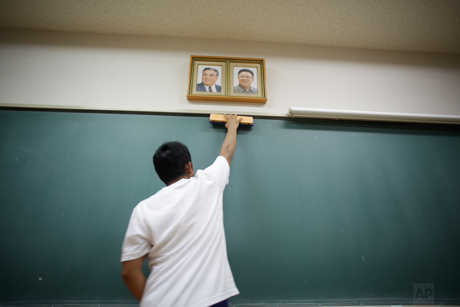 In this Sept. 26, 2017, photo, a student cleans the blackboard under the portraits of the late North Korean leaders Kim Il Sung and Kim Jong Il hanging in classroom at a Korean high school in Tokyo.  (AP Photo/Eugene Hoshiko)