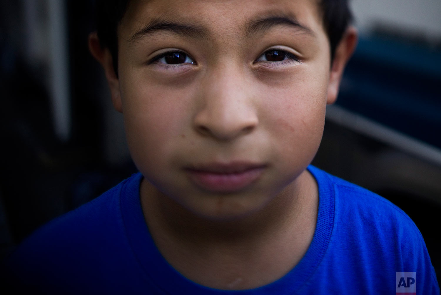 John Ruiz, 9, pauses for photos in front of his RV he and his family live in Monday, Oct. 23, 2017, in Mountain View, Calif. Ruiz lives in an RV with his parents and four siblings after they could no longer afford the rent. Ruiz said he wants to make a lot of money and spend it with his family. (AP Photo/Jae C. Hong)