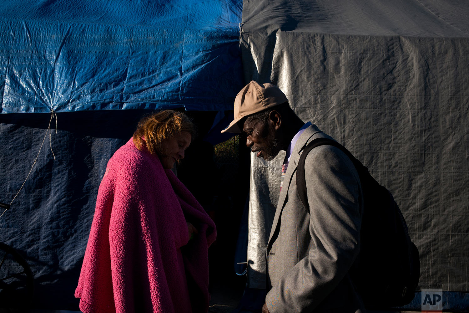 Two homeless people, Tammy Stephen, 54, left, and Bennie Koffa, 66, walk past each other at Camp Second Chance, a city-sanctioned homeless encampment, Tuesday, Sept. 26, 2017, in Seattle. Against the backdrop of its booming economy, the West Coast is experiencing another type of boom_a massive surge in homeless people living on the streets that in many places is beginning to overwhelm the ability of local governments to deal with it. (AP Photo/Jae C. Hong)