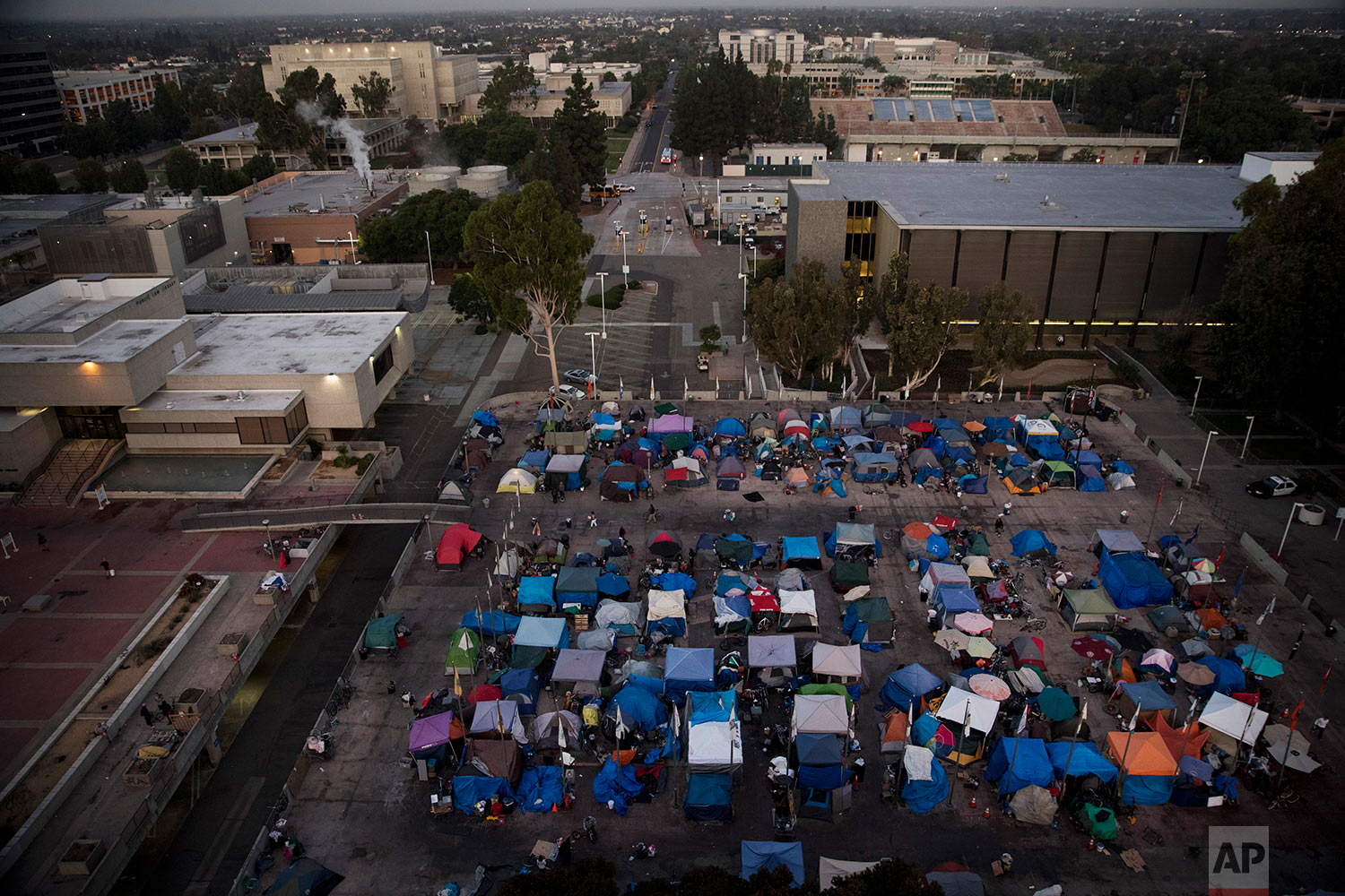 "A large homeless encampment is formed on the ""Plaza of the Flags"" elevated park at the Santa Ana Civic Center complex Wednesday, Oct. 11, 2017, in Santa Ana, Calif. California declared a statewide emergency due to a hepatitis A outbreak linked to homeless encampments. Comparisons are being made to conditions more commonly seen in Third World countries. (AP Photo/Jae C. Hong)"