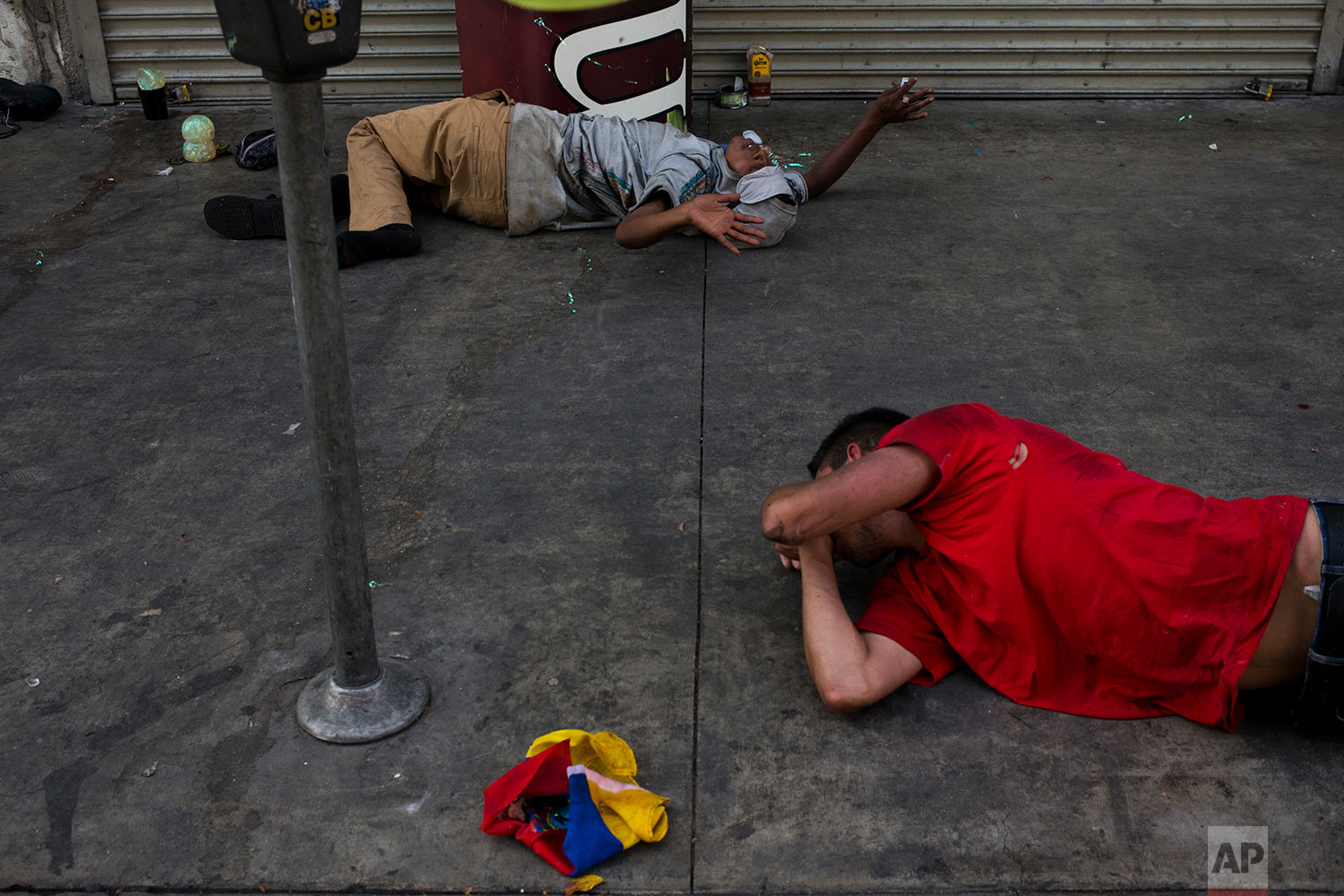 Lying on a urine-stained sidewalk, two homeless drug addicts, high on drugs, hallucinate in Los Angeles' Skid Row area, home to the nation's largest concentration of homeless people, Friday, Sept. 1, 2017. According to Midnight Mission's Joey Weinert, a former drug addict who now helps homeless people fight their addictions, said many homeless use drugs and alcohol to cope with their lives. (AP Photo/Jae C. Hong)