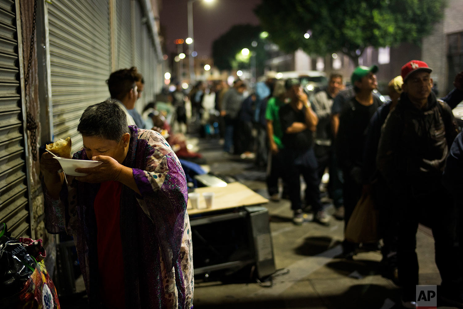 A homeless woman, who declined to give her name, eats chicken soup with a piece of bread while others wait in line for food Wednesday, Sept. 20, 2017, in downtown Los Angeles. According to the annual count released in May by the Los Angeles Homeless Services Authority, Los Angeles County's homeless population has increased to 57,794, a 23 percent jump from last year's count. (AP Photo/Jae C. Hong)