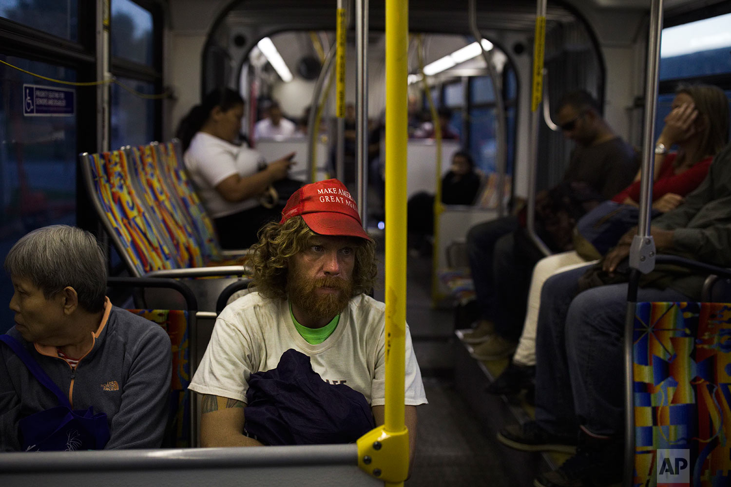 "Wearing a ""Make America Great Again"" hat, Nathanael Baisley, 38, sits in a bus in Los Angeles en route to Santa Monica Beach, where he spends the night, Saturday, Oct. 28, 2017. Baisley said he has been homeless on and off for three years and is going through a divorce with his wife who lives in England with their 5-year-old son. (AP Photo/Jae C. Hong)"