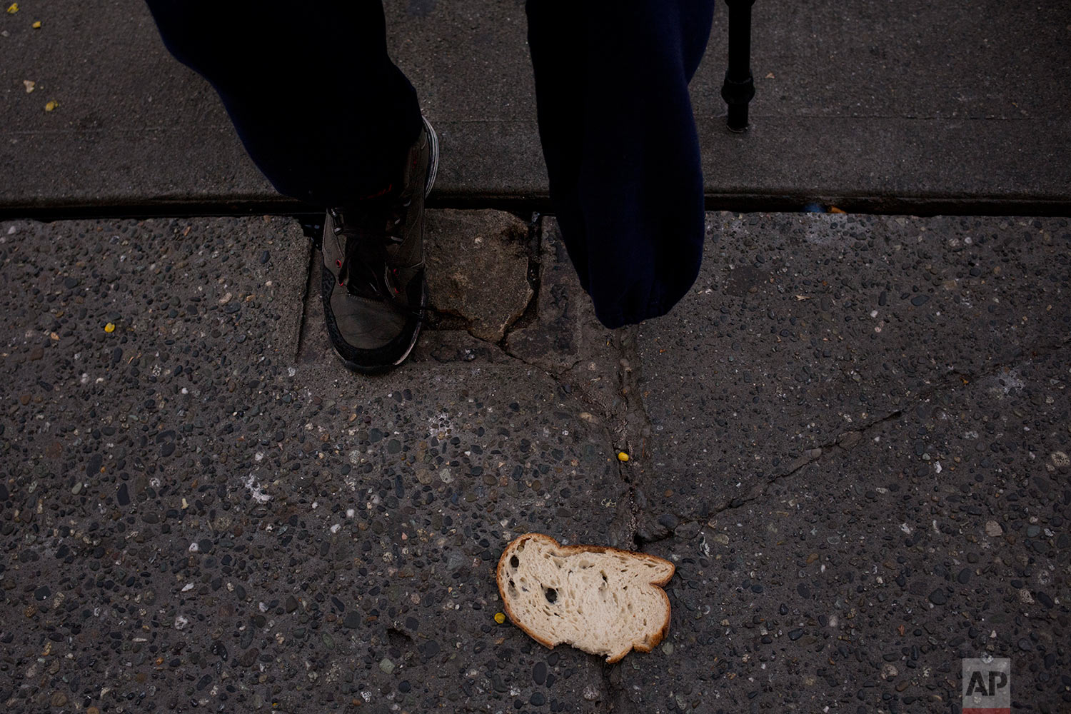 "A piece of bread is left on a sidewalk as Korey Epps, a 44-year-old homeless man who had his leg amputated due to an infection while in jail, waits in line to enter Seattle's Union Gospel Mission to spend the night at the shelter Wednesday, Sept. 27, 2017, in Seattle. Serving 14 months in jail, Epps said he lost his job, family and home. ""Everyday I feel more more worthless, hopeless. I can't believe this is where my life is,"" said Epps. ""I may as well be on drugs because I lost everything."" (AP Photo/Jae C. Hong)"