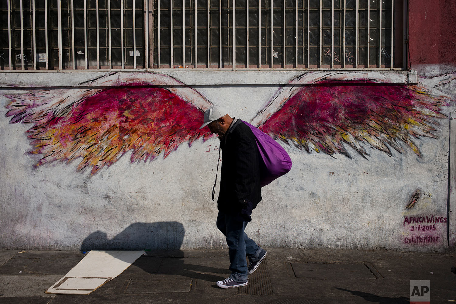 "A man walks past a mural of angel wings titled ""Africa Wings"" by artist Colette Miller in Los Angeles' Skid Row area, home to the nation's largest concentration of homeless people, Friday, Sept. 1, 2017. According to the annual count released in May by the Los Angeles Homeless Services Authority, Los Angeles County's homeless population has increased to 57,794, a 23 percent jump from last year's count. (AP Photo/Jae C. Hong)"