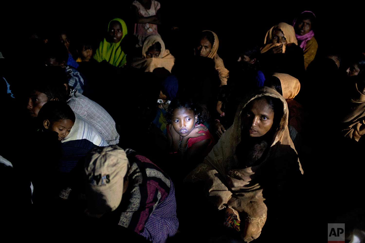 While waiting for permission to proceed forward, the beam of a flashlight illuminates the face of a Rohingya Muslim girl sitting with a group in a raft made of plastic containers on which they crossed over from Myanmar into Bangladesh, near Shah Porir Dwip, Bangladesh, Friday, Nov. 10, 2017. U.N. (AP Photo/A.M. Ahad)