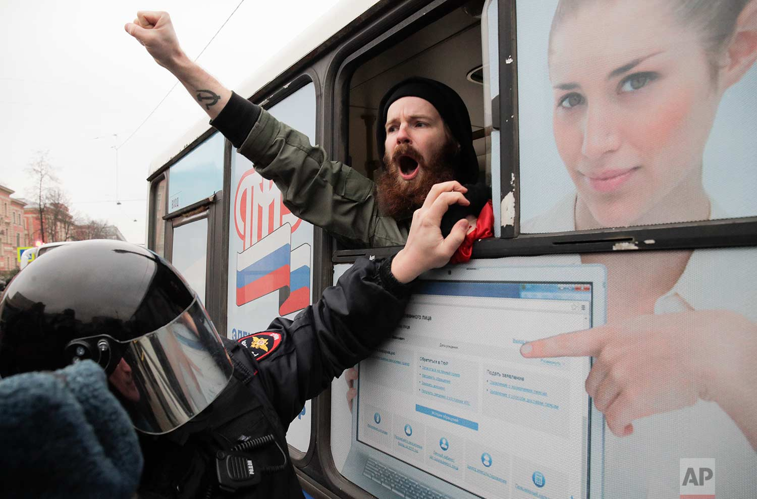A detained member of the Other Russia movement shouts from a police bus during an unauthorized rally to mark the centenary of the Bolshevik Revolution in St. Petersburg, Russia, on Monday, Nov. 6, 2017. (AP Photo/Dmitri Lovetsky)