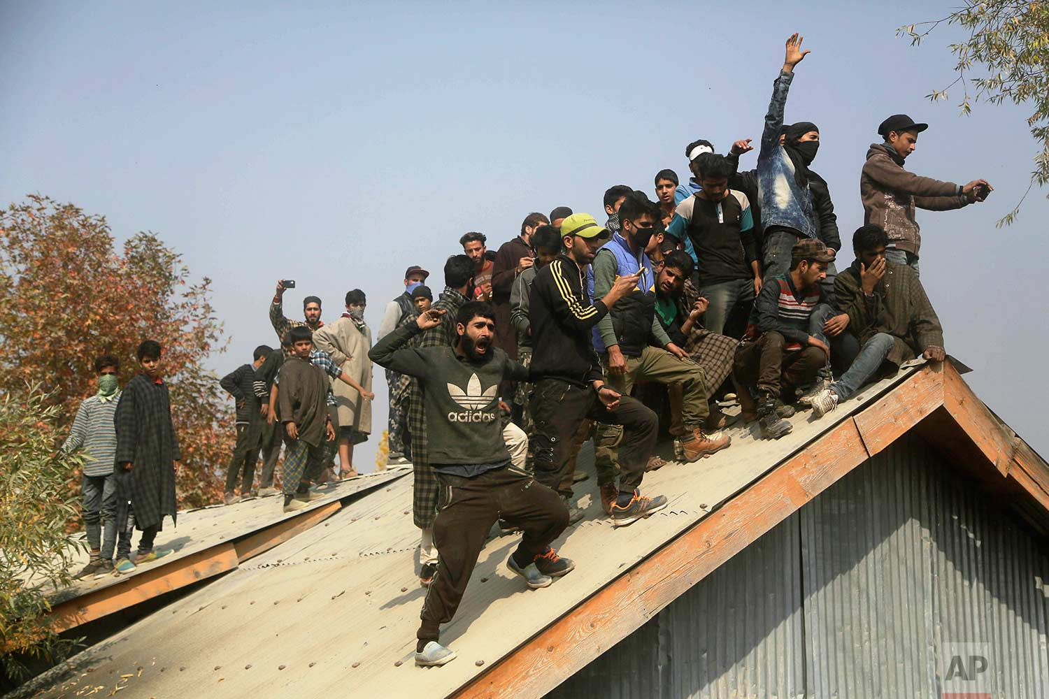 Kashmiri villagers shout pro-freedom slogans from a roof during the funeral procession for killed militant Waseem Ahmad in Drubgam, 48 kilometers (30 miles) south of Srinagar, Indian controlled Kashmir, Tuesday, Nov. 7, 2017. (AP Photo/Mukhtar Khan)
