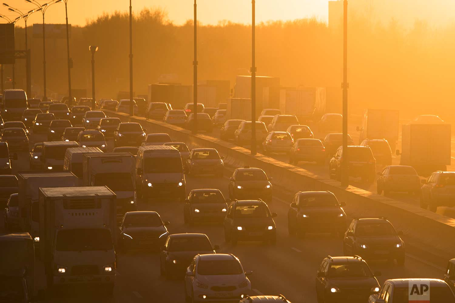 Cars stuck in traffic travel on a road in Moscow, Russia during sunset on Wednesday, Nov. 8, 2017. (AP Photo/Pavel Golovkin)