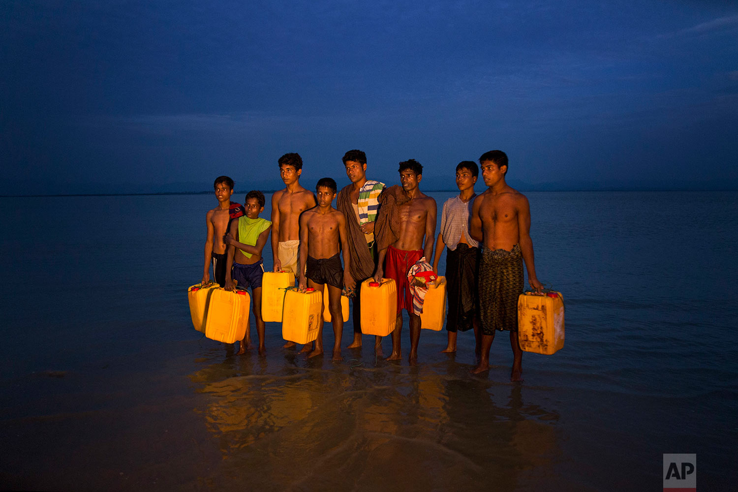 In this Nov. 5, 2017, photo, newly arrived Rohingya Muslims carry yellow plastic drums they used as flotation aids and listen to Bangladeshi authorities, not pictured, after swimming across the Naf river at Shah Porir Dwip, Bangladesh. (AP Photo/Bernat Armangue)