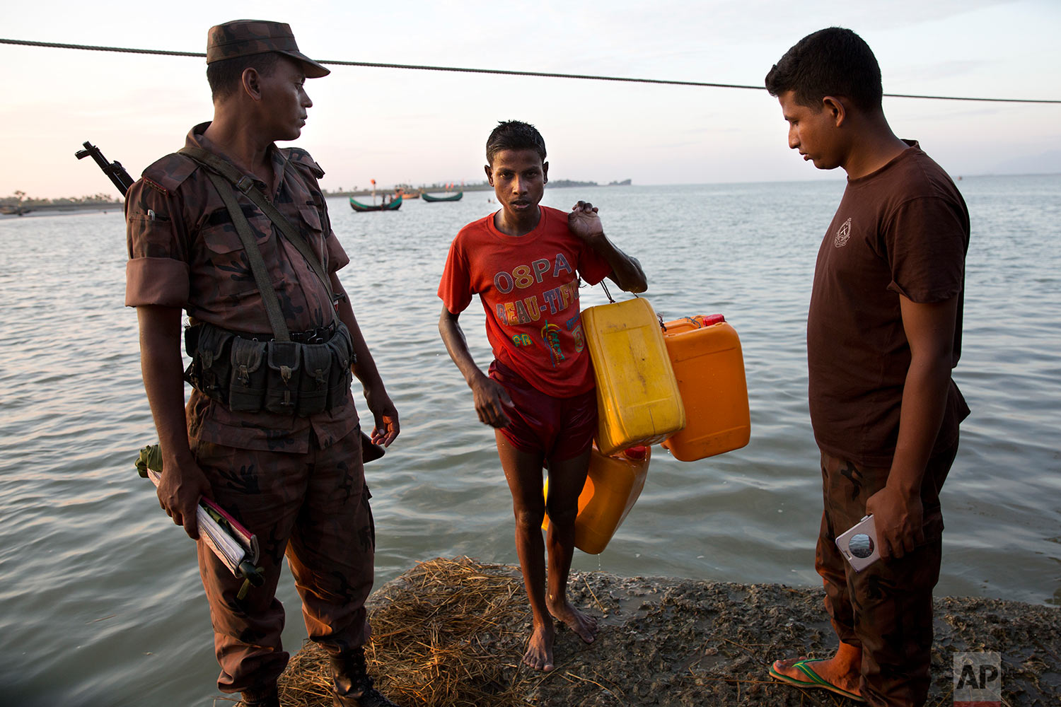 In this Nov. 4, 2017, photo, a Bangladeshi border guard, left, looks at a Rohingya Muslim Belal Hussain, 15, center, as he steps out of the water carrying yellow plastic drums he used as a flotation aid at Shah Porir Dwip, Bangladesh, after swimming the Naf river. (AP Photo/Bernat Armangue)