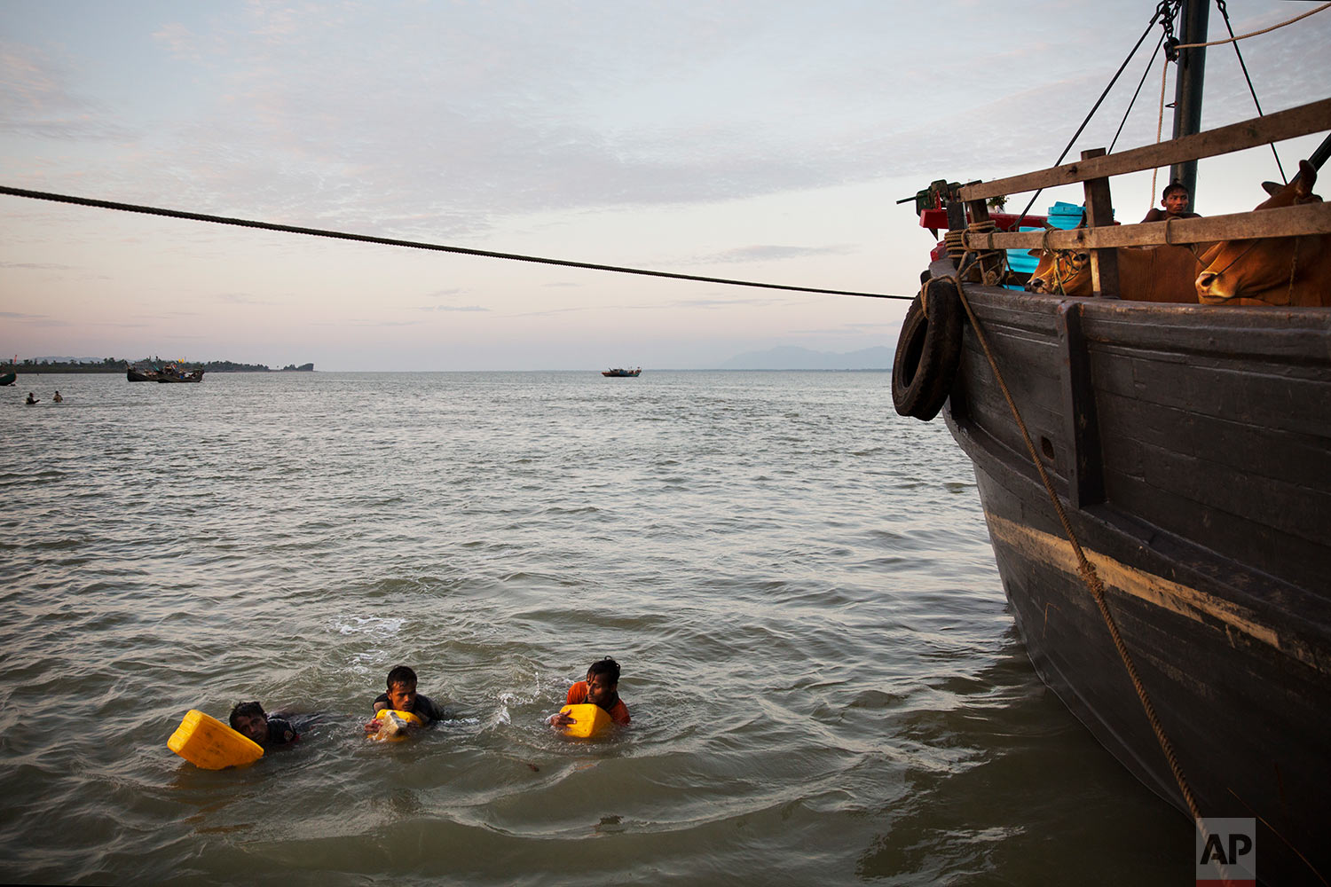 In this Nov. 4, 2017, photo, Rohingya Muslims use yellow plastic drums as flotation devices as they arrive at Shah Porir Dwip, Bangladesh, after swimming the Naf river. The Naf river is a natural border between Myanmar and Bangladesh. The boys stepped into the water just as the current started to shift toward Bangladesh, tied together with ropes in groups of three. (AP Photo/Bernat Armangue)