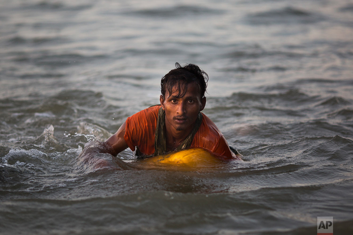 In this Nov. 4, 2017, photo, Rohingya Muslim Abdul Karim, 19, uses a yellow plastic oil container as a flotation device as he swims the Naf river while crossing the Myanmar-Bangladesh border in Shah Porir Dwip, Bangladesh. (AP Photo/Bernat Armangue)