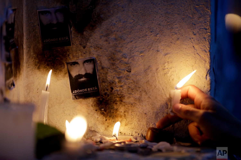 A woman lights a candle near a photo of missing activist Santiago Maldonado at a makeshift memorial outside the morgue in Buenos Aires, Argentina, Saturday, Oct. 21, 2017.(AP Photo/Natacha Pisarenko)