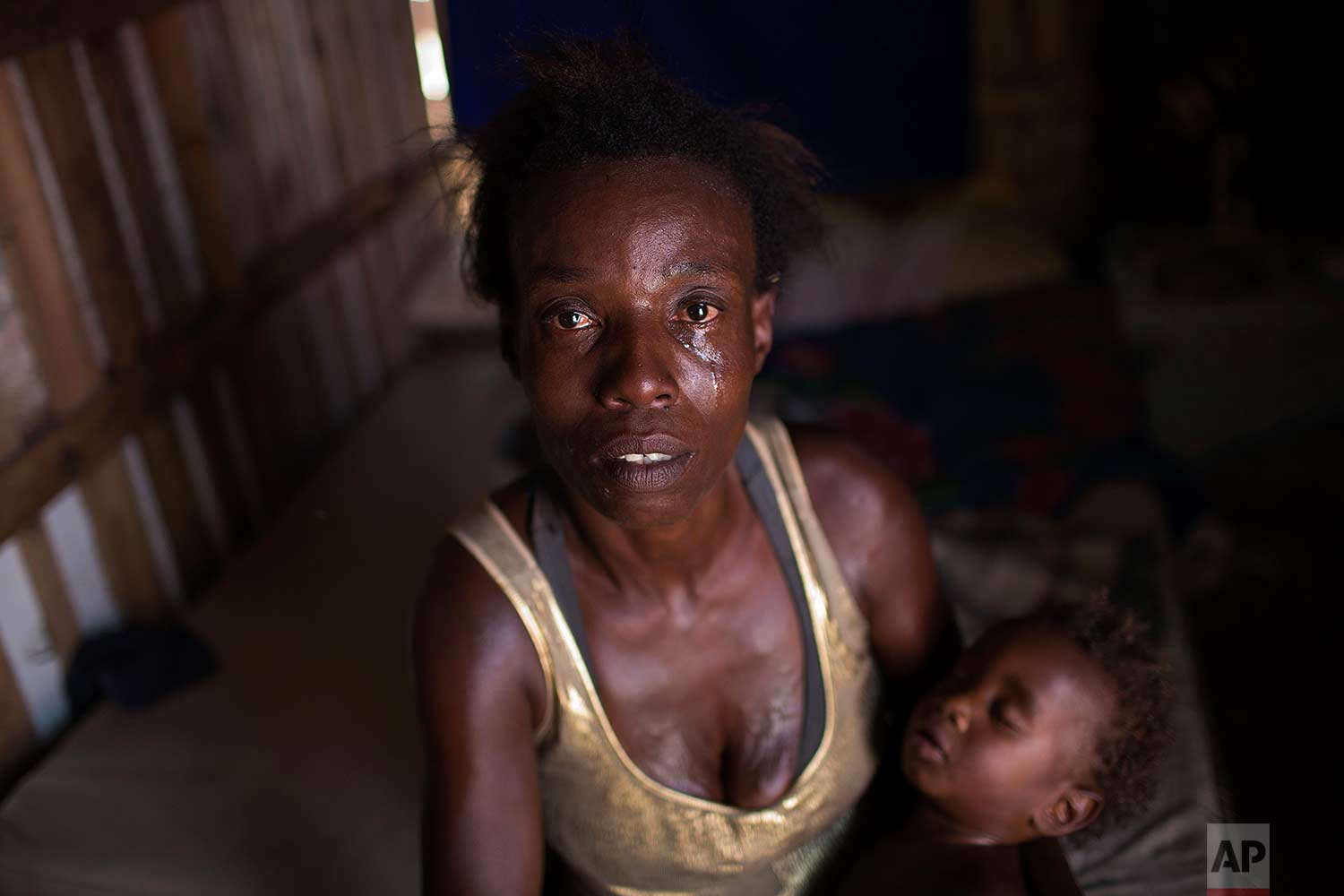 """In this Oct. 20, 2017 photo, Simone Batista, holding her baby Arthur, looks into the camera as tears roll down her cheeks while she recounts being cut from the """"Bolsa Familia"""" government subsidy program for low-income people, at her shack home in the Jardim Gramacho slum of Rio de Janeiro, Brazil. (AP Photo/Silvia Izquierdo)"""