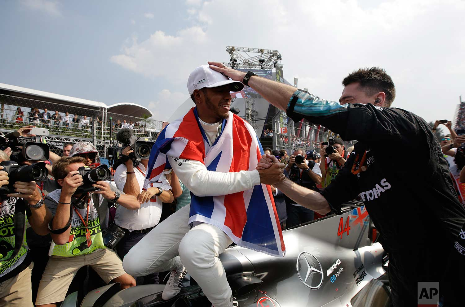 British driver Lewis Hamilton celebrates wining his fourth Formula One championship with a member of his team after the Mexican Formula One Grand Prix auto race at the Hermanos Rodriguez racetrack in Mexico City, Sunday, Oct. 29, 2017. (AP Photo/Moises Castillo)