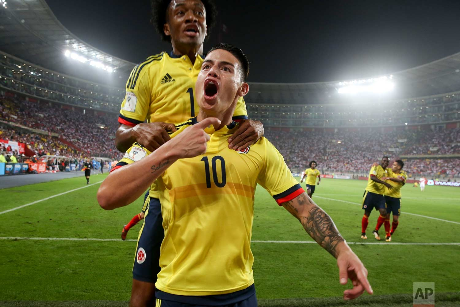 Colombia's James Rodriguez, front, celebrates after scoring against Peru as teammate Juan Cuadrado jumps behind him during a 2018 World Cup qualifying soccer match in Lima, Peru, Tuesday, Oct. 10, 2017. (AP Photo/Martin Mejia)