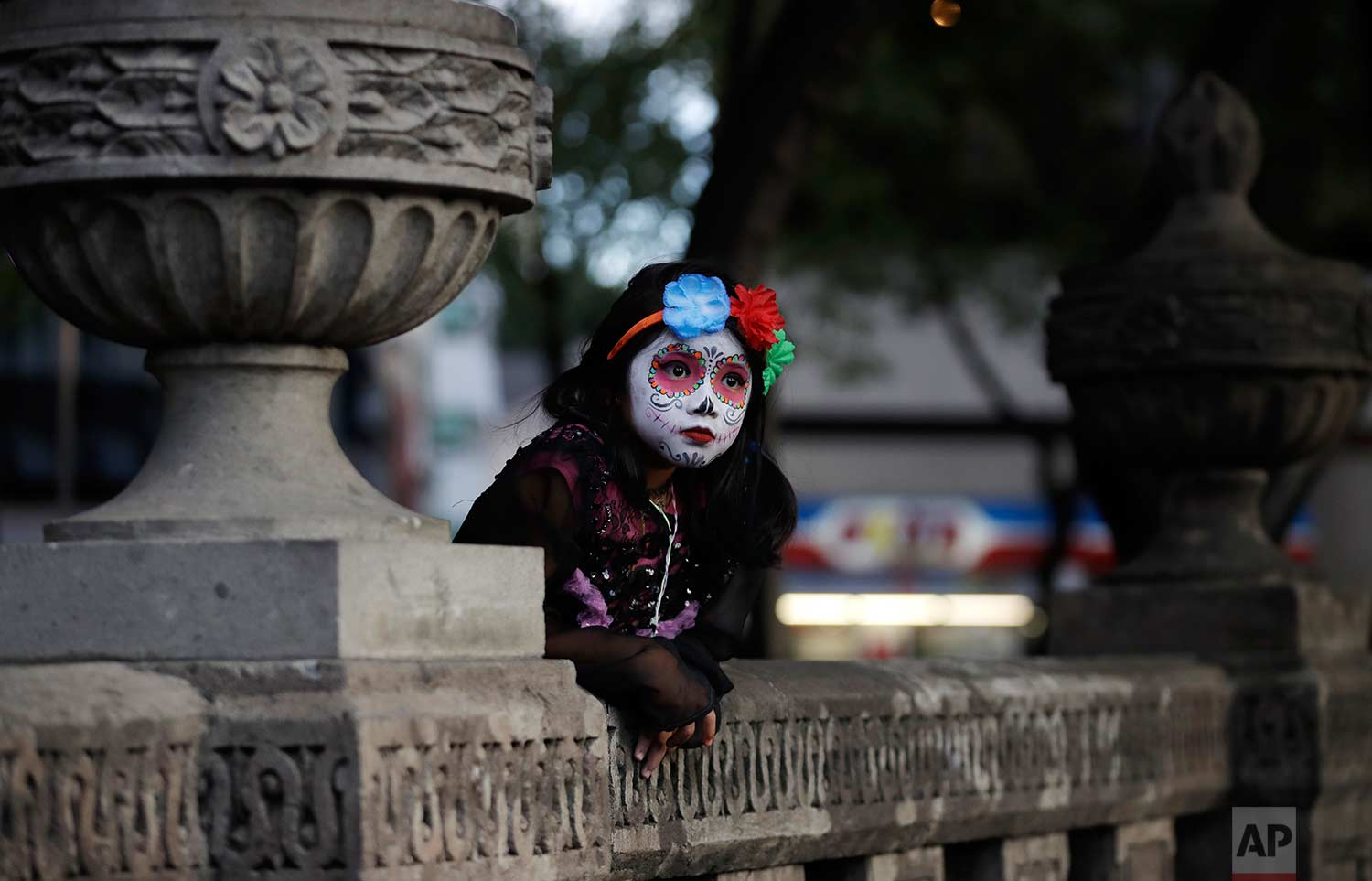 """A girl dressed as Mexico's iconic """"Catrina"""" leans against stone benches as she awaits the start of the Grand Procession of the Catrinas, part of upcoming Day of the Dead celebrations in Mexico City, Sunday, Oct. 22, 2017. (AP Photo/Rebecca Blackwell)"""