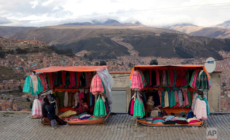 Traditional Andean women's skirts hang for sale at vendors' stores set up along the road between El Alto and La Paz, Bolivia, Thursday, Oct. 12, 2017. (AP Photo/Juan Karita)