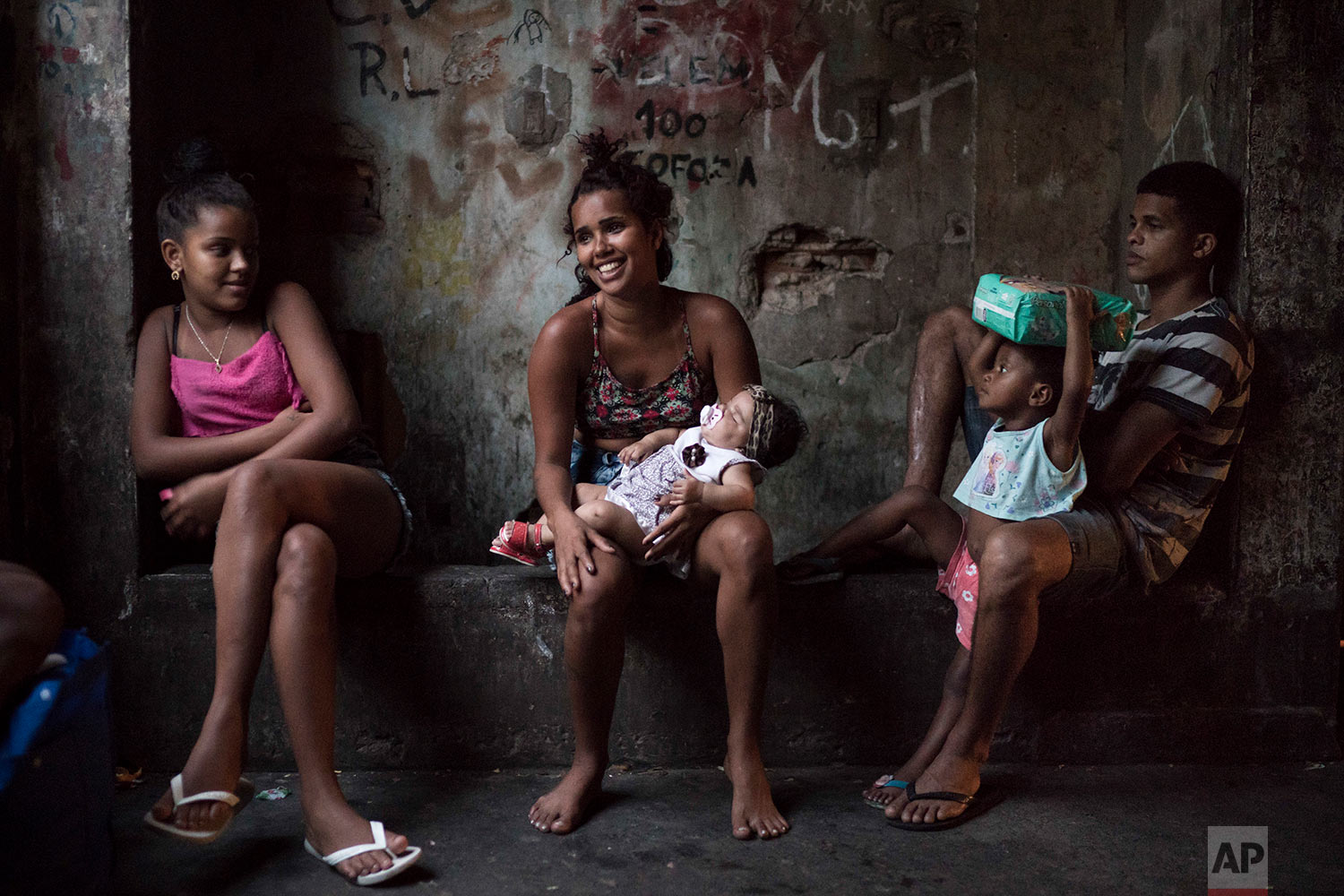 In this Sept. 9, 2017 photo, residents sit in a corridor inside a squatter building that used to house the Brazilian Institute of Geography and Statistics (IBGE) in the Mangueira slum of Rio de Janeiro, Brazil. Despite the hardscrabble existence, there is a strong sense of community among the hundreds of people occupying the building. (AP Photo/Felipe Dana)