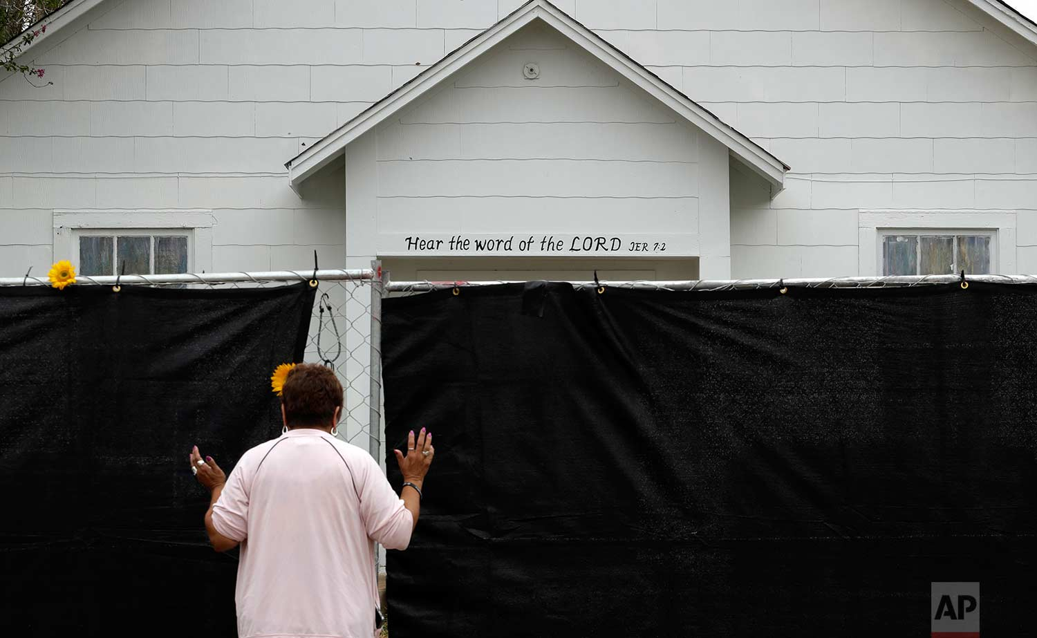A woman prays next to a fence outside the Sutherland Springs First Baptist Church, Sunday, Nov. 12, 2017, in Sutherland Springs, Texas, a week after a man opened fire inside the church. (AP Photo/Eric Gay)