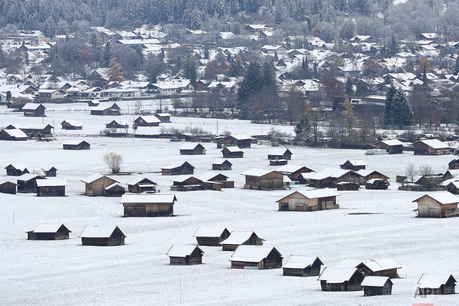 First snow of the season covers wooden cottages in Garmisch-Partenkirchen, Germany, Monday, Nov. 13, 2017. (AP Photo/Matthias Schrader)