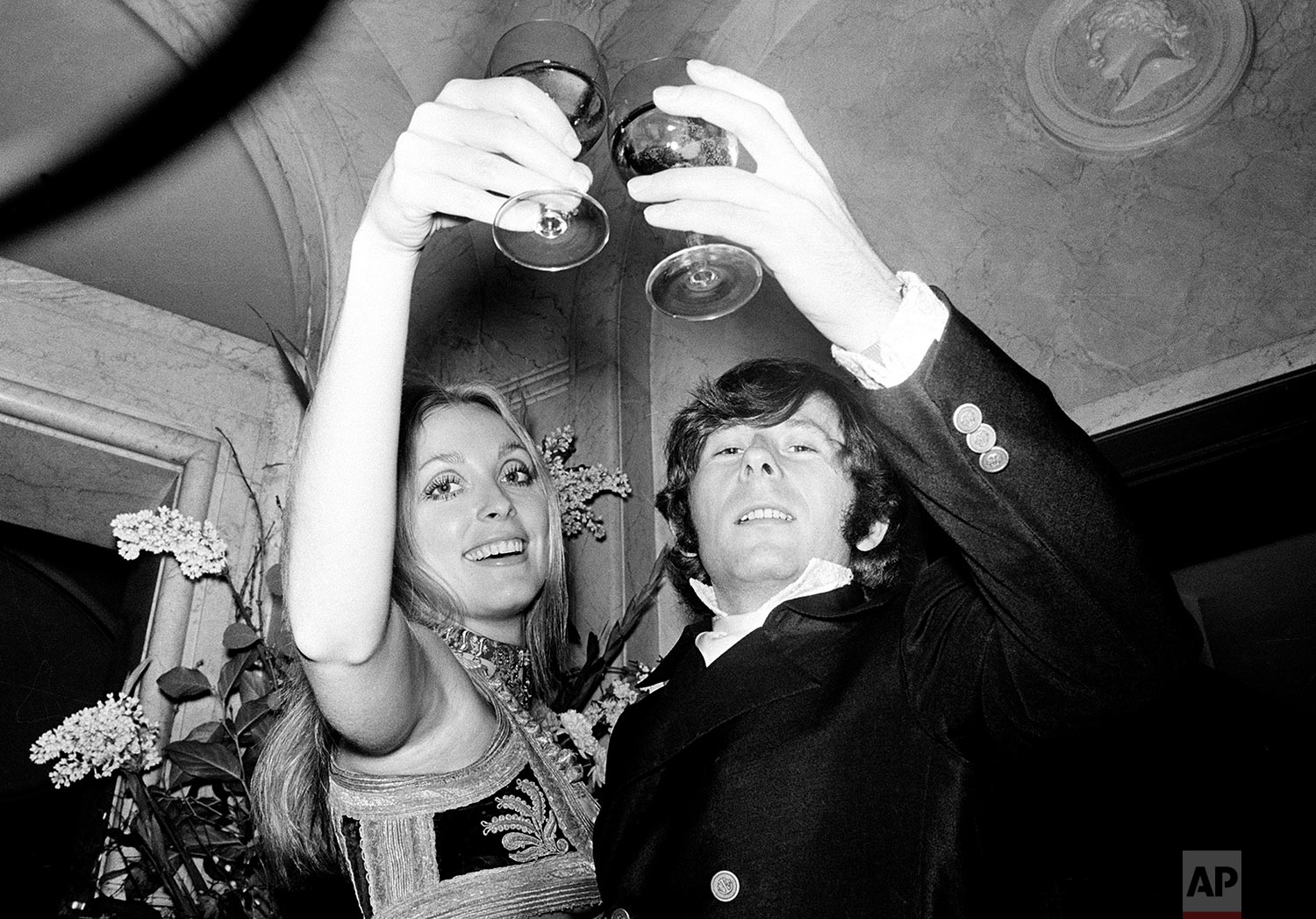 """Film director Roman Polanski and his wife, actress Sharon Tate, lift their glasses in a toast at the premiere of his film """"Rosemary's Baby"""" in London, England, Jan. 23, 1969. (AP Photo)"""