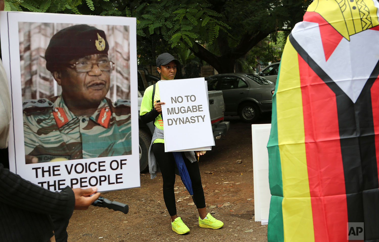 People hold their messages in Harare to demonstrate for the ouster of President Robert Mugabe who is virtually powerless and deserted by most of his allies, Saturday, Nov. 18, 2017. Zimbabwe's generals, including Constantino Chiwenga, on poster left, have placed Mugabe under house arrest and have allowed him limited movement while talks on his exit from office unfold. (AP Photo/Tsvangirayi Mukwazhi)