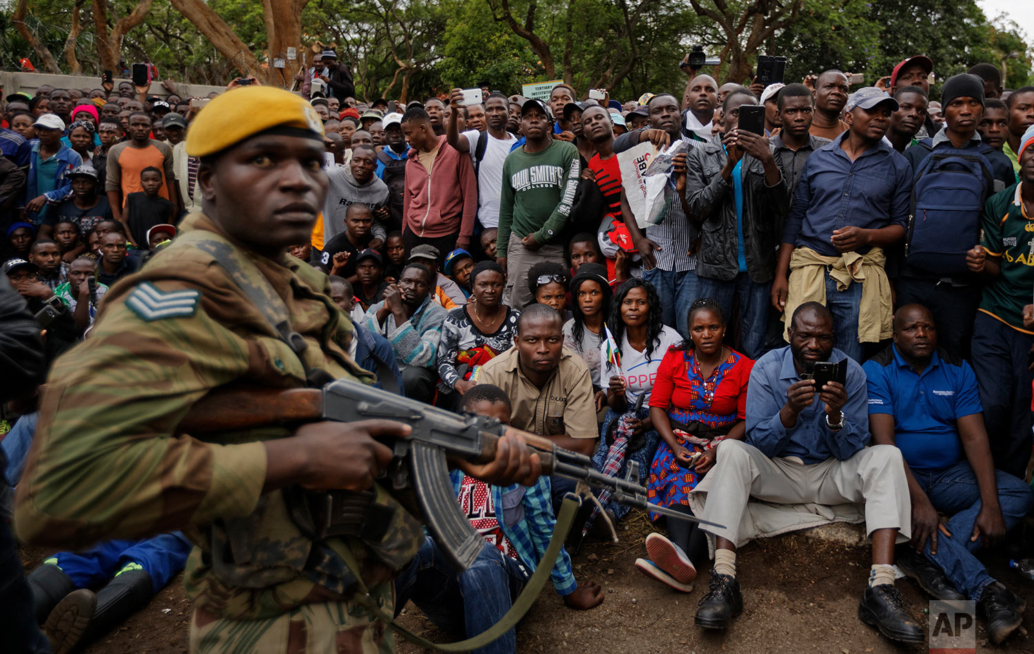 An army soldier stands guard as protesters demanding President Robert Mugabe stands down gather on the road leading to State House in Harare, Zimbabwe Saturday, Nov. 18, 2017. In a euphoric gathering that just days ago would have drawn a police crackdown, crowds marched through Zimbabwe's capital on Saturday to demand the departure of President Robert Mugabe, one of Africa's last remaining liberation leaders, after nearly four decades in power. (AP Photo/Ben Curtis)
