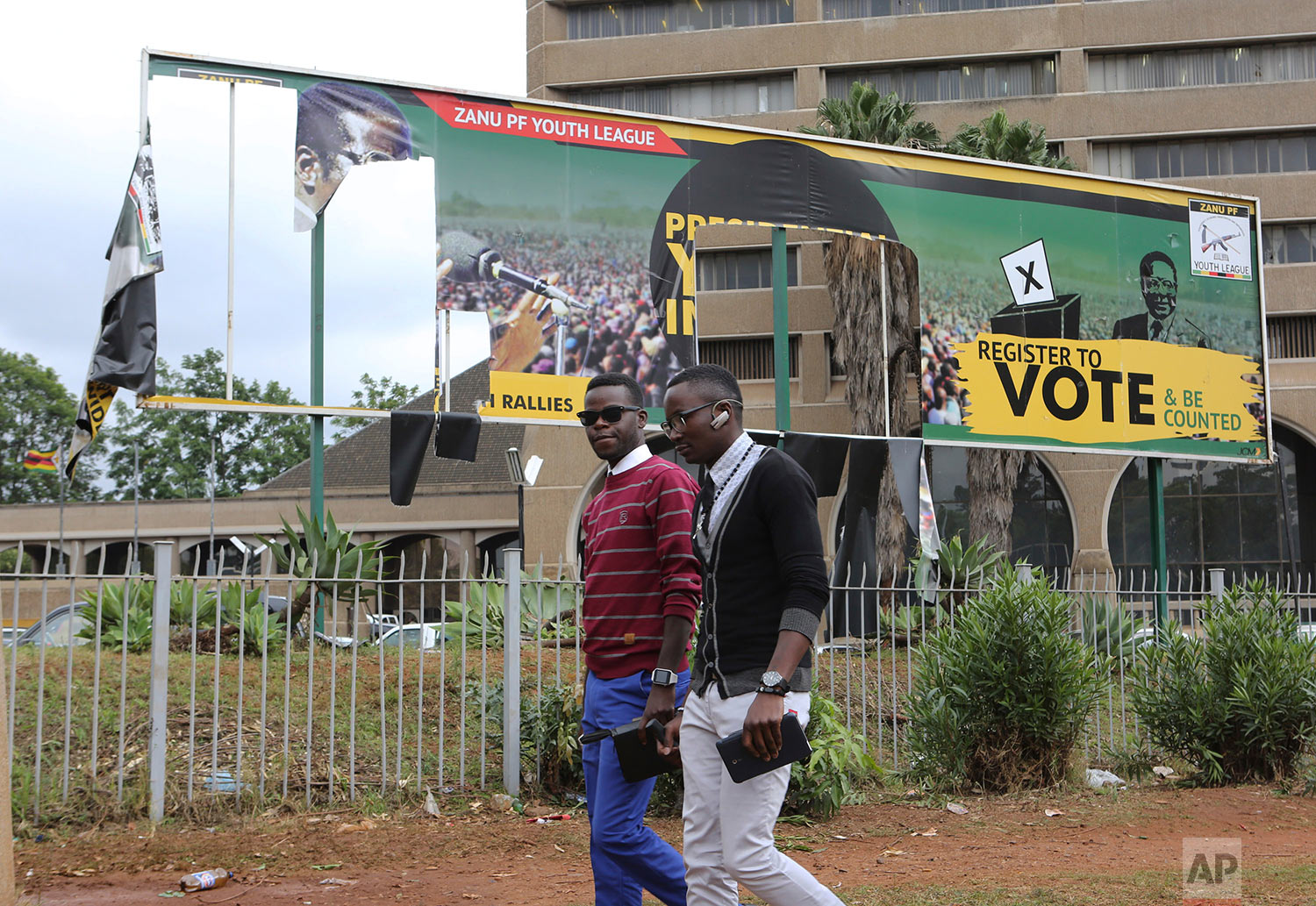 People walk past a partly torn down ruling party banner that showed Zimbabwe President Robert Mugabe's face at the Zanu pf headquarters in Harare, Zimbabwe Sunday Nov. 19, 2017.  Clinging to his now virtually powerless post, longtime President Mugabe on Sunday was set to discuss his expected exit with the army commander who put him under house arrest, while the ruling party prepared to recall the world's oldest head of state as its leader. (AP Photo/Tsvangirayi Mukwazhi)