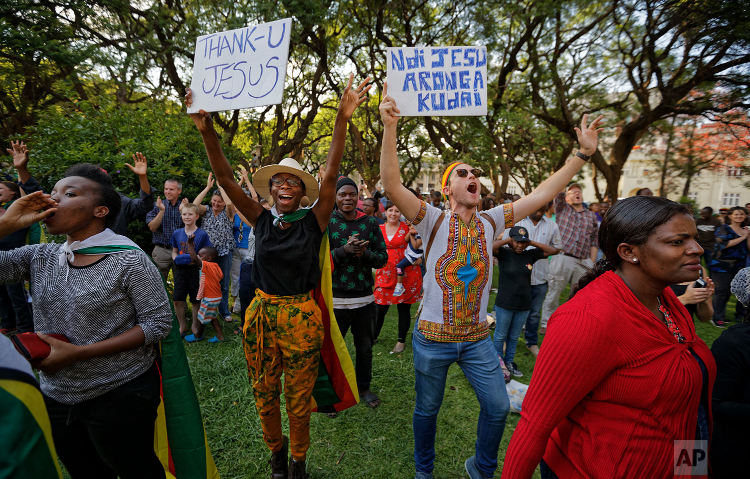 "Zimbabweans sing and pray at a Christian peace and prayer rally in downtown Harare, Zimbabwe Sunday, Nov. 19, 2017. A day after huge crowds rallied peacefully in the capital for 93-year-old President Robert Mugabe to step down, Zimbabweans around the country attended Sunday church services and peace rallies, praying for the future of their country. Sign in Shona at right reads ""It was Jesus who planned it"". (AP Photo/Ben Curtis)"