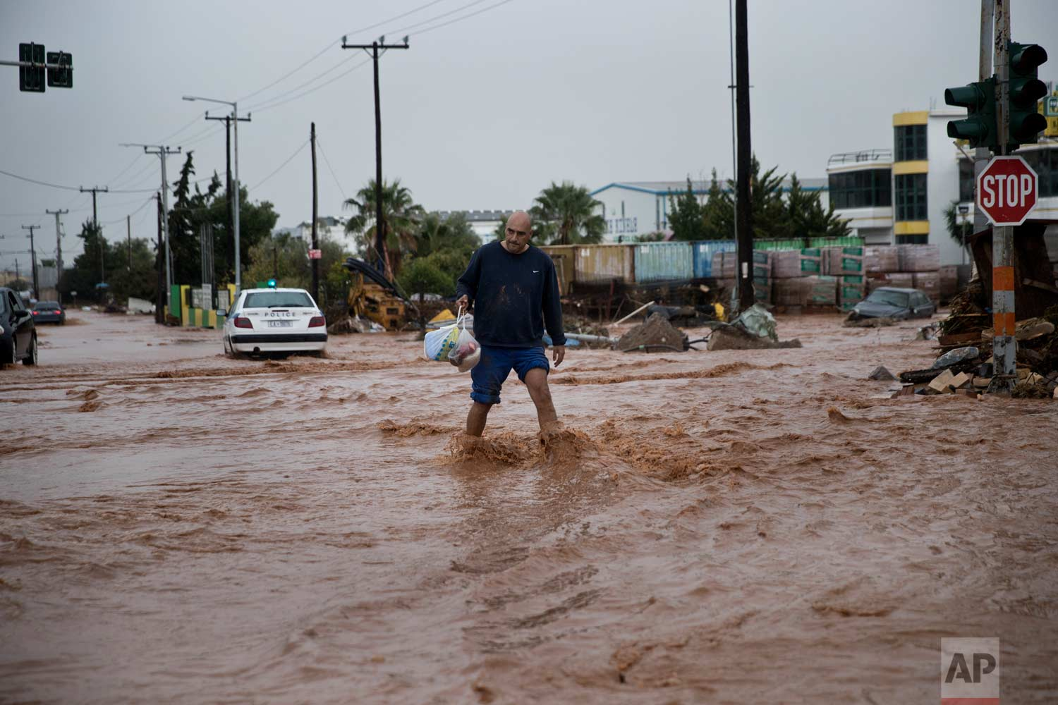 In this Wednesday, Nov. 15, 2017 photo a man walks on a flooded street in the town of Mandra western Athens. (AP Photo/Petros Giannakouris)