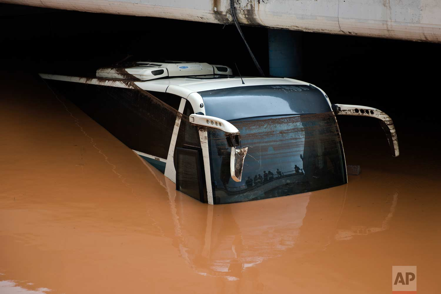 In this Wednesday, Nov. 15, 2017 photo people are reflected on the front window of a flooded bus as water covers an interchange of a highway in Elefsina, west of Athens. Flash floods in the Greek capital's western outskirts Wednesday turned roads into raging torrents of mud and debris, killing at least twenty people, inundating homes and businesses and knocking out a section of a highway. (AP Photo/Petros Giannakouris)