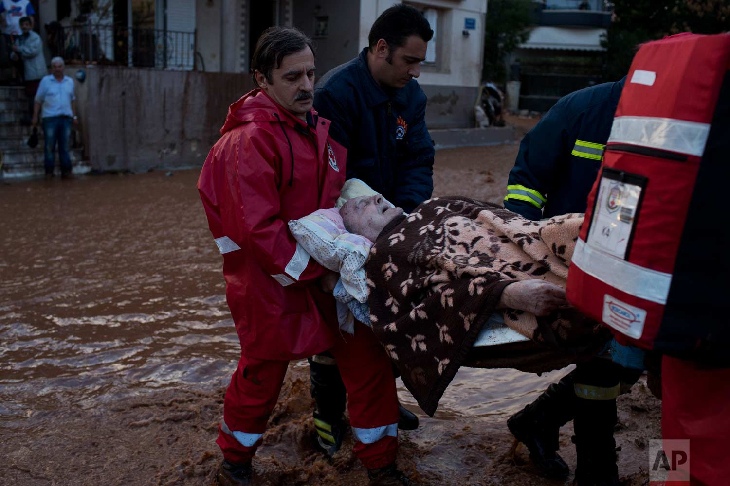 In this Wednesday, Nov. 15, 2017 photo, Red Cross personnel and firefighters carry an elderly man to an ambulance in town of Mandra western Athens, following deadly flash floods that hit the area. (AP Photo/Petros Giannakouris)
