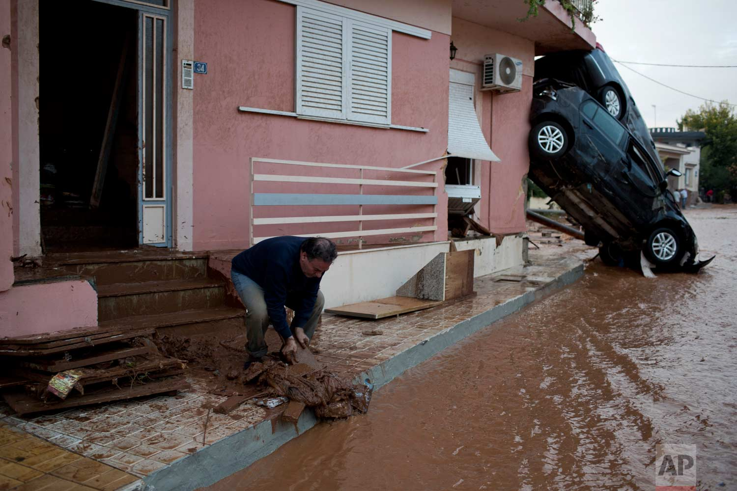In this Wednesday, Nov. 15, 2017 photo, a man clears mad from his home in front of flipped over cars in the town of Mandra western Athens, following deadly flash floods that hit the area. Nearly 1,000 buildings were damaged, most of them private houses, as well as businesses, storage areas and public buildings.(AP Photo/Petros Giannakouris)