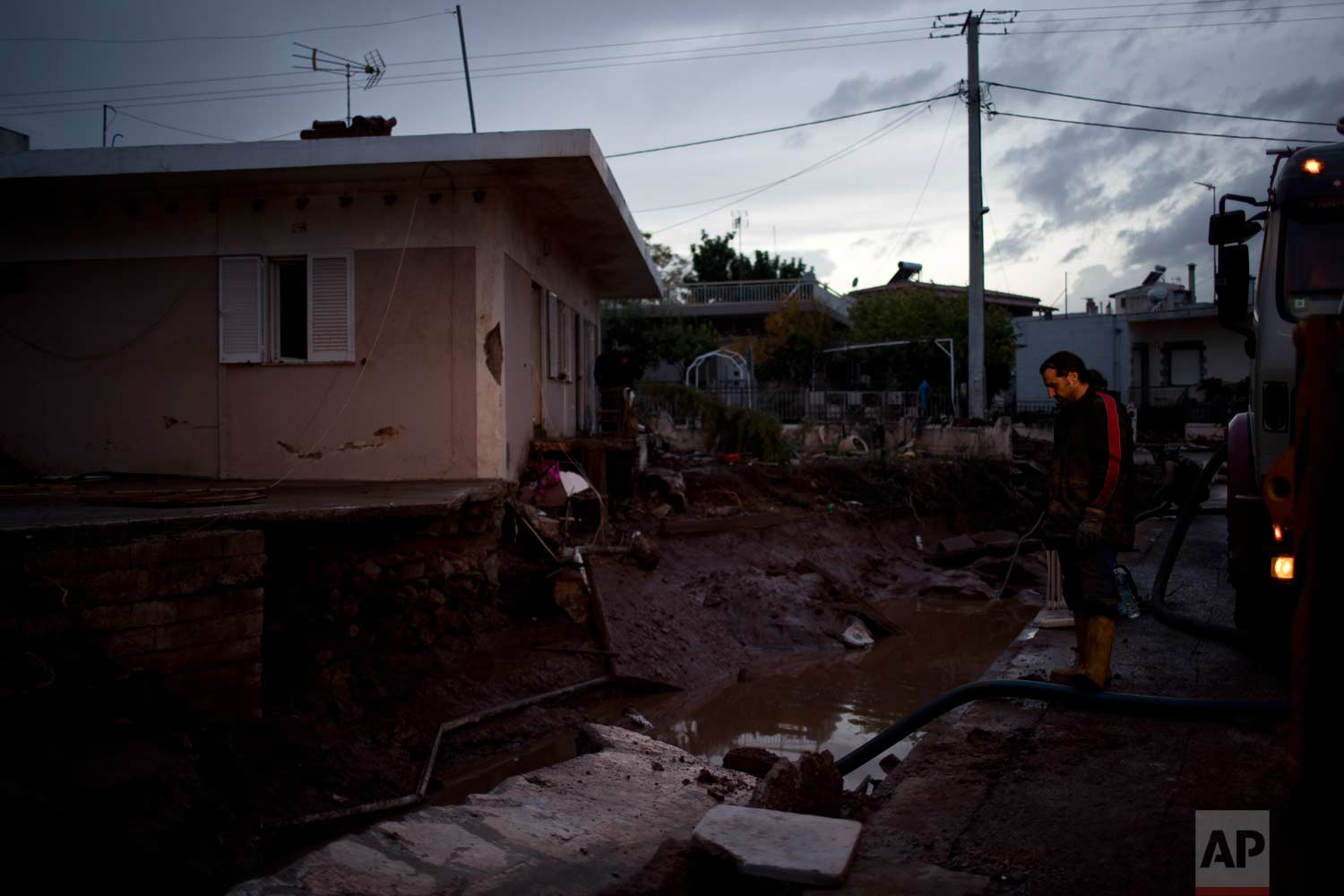 In Thursday, Nov. 16, 2017 photo worker uses a hose to suck up water from a damaged yard of a house in the town of Mandra western Athens following major flash flooding on Wednesday that left at least 21 people dead.(AP Photo/Petros Giannakouris)
