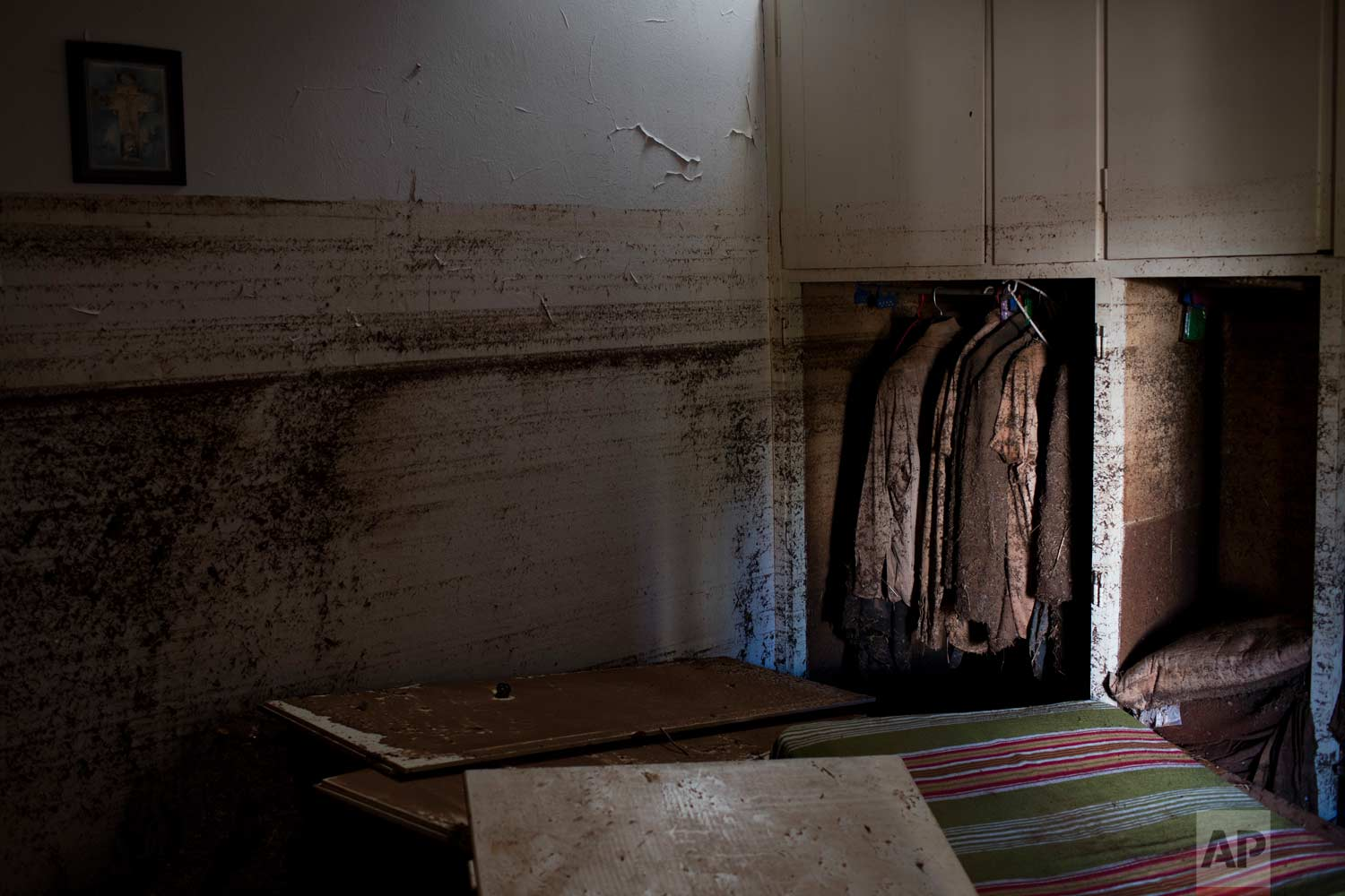 In this Tuesday, Nov. 21, 2017 photo clothes covered with mud are hunged in a closet into a flood-damaged home in the town of Mandra , west of Athens.(AP Photo/Petros Giannakouris)