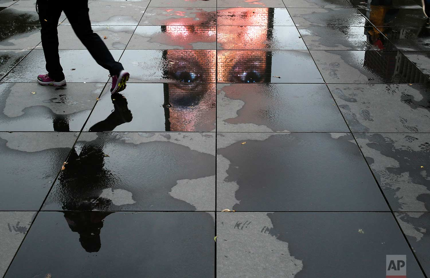 A pedestrian walks through puddles reflecting a projected face displayed on a video sculpture at the Crown Fountain in Chicago's Millennium Park, Tuesday, Nov. 21, 2017, in Chicago. (AP Photo/Charles Rex Arbogast)