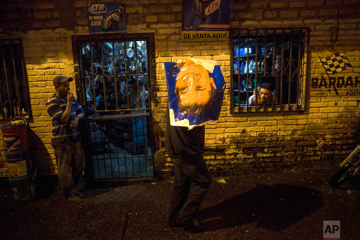 A man protects himself from the rain with a political campaign banner promoting Honduras President and current presidential candidate Juan Orlando Hernandez, in Tegucigalpa, Honduras, Wednesday, Nov. 22, 2017. (AP Photo/Rodrigo Abd)