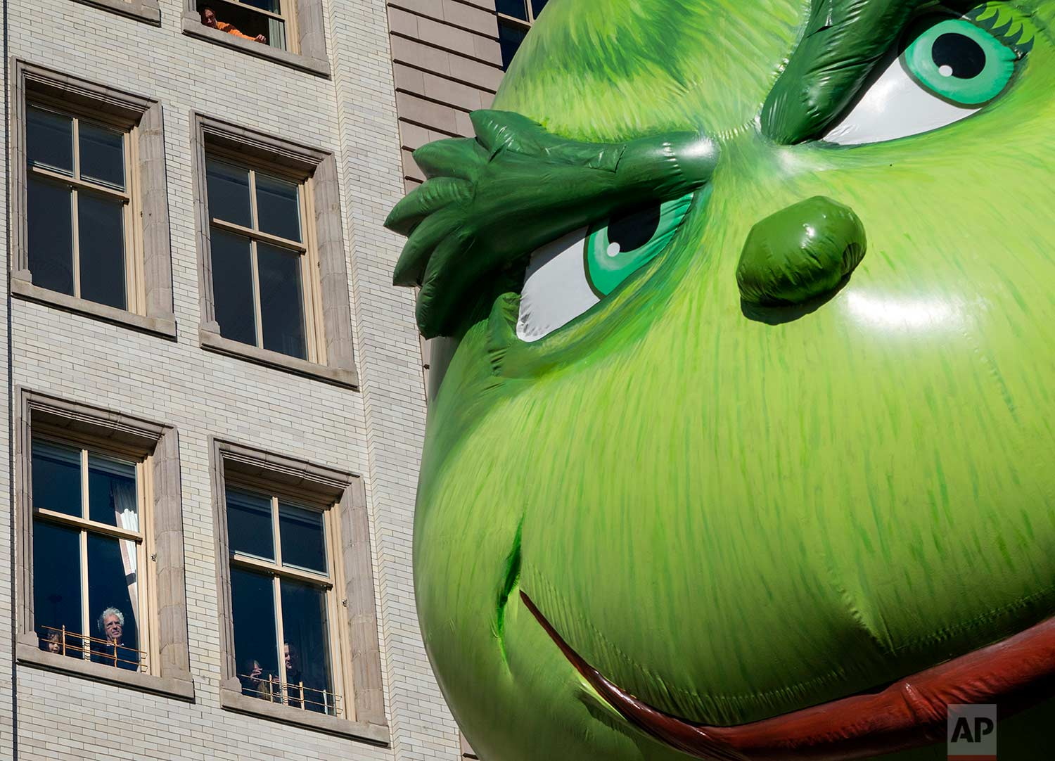 The Grinch balloon passes by windows of a building on Central Park West during Macy's Thanksgiving Day Parade in New York Thursday, Nov. 23, 2017. (AP Photo/Craig Ruttle)