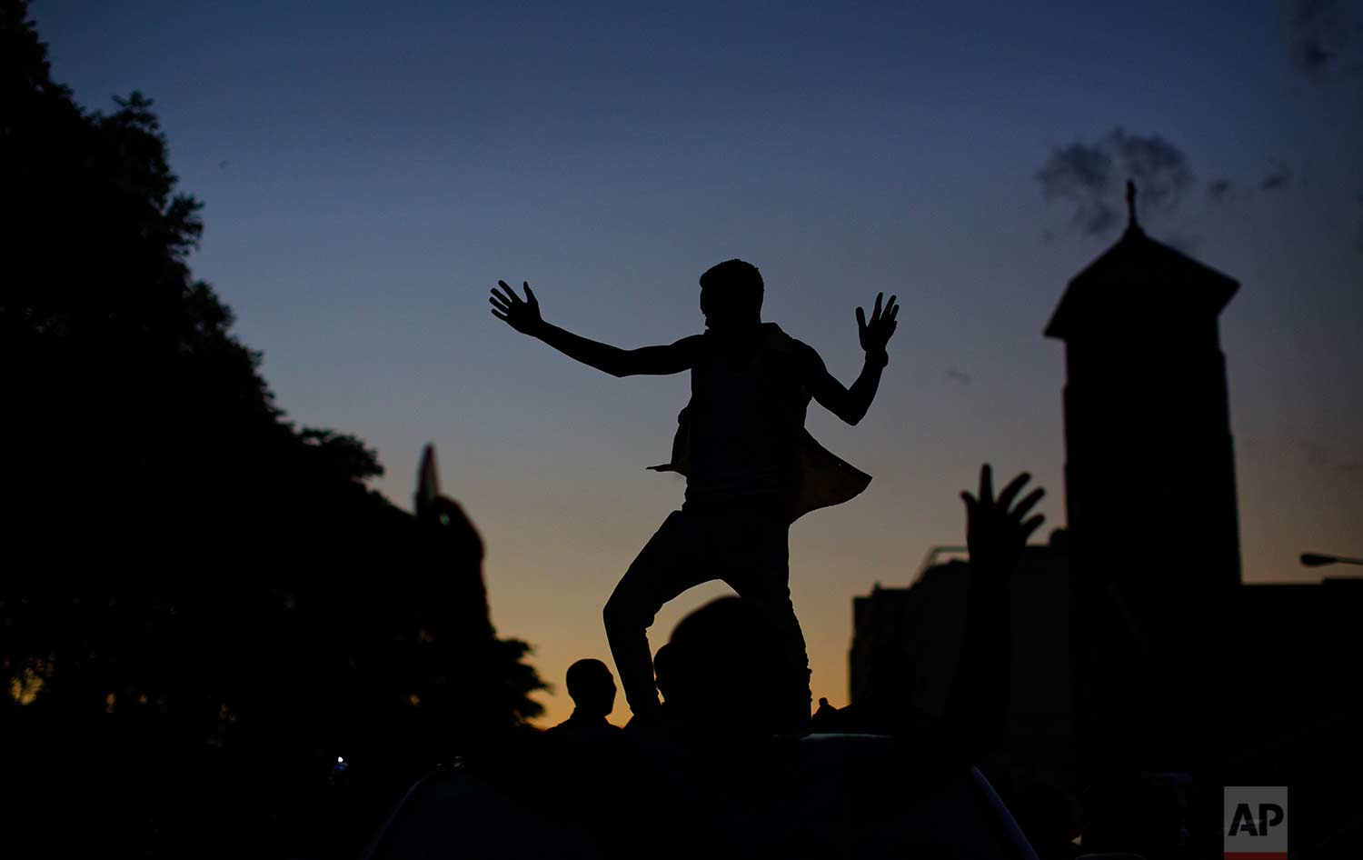 A Zimbabwean dances on the roof of a vehicle as he and others celebrate outside the parliament building immediately after hearing the news that President Robert Mugabe had resigned, in downtown Harare, Zimbabwe Tuesday, Nov. 21, 2017. (AP Photo/Ben Curtis)