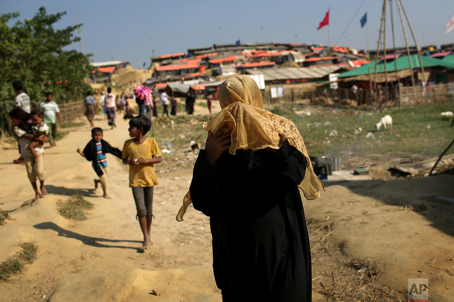 A Rohingya Muslim woman covers her face from the afternoon dust and heat as she walks through Jamtoli refugee camp on Monday, Nov. 27, 2017, in Bangladesh. Since late August, more than 620,000 Rohingya have fled Myanmar's Rakhine state into neighboring Bangladesh, where they are living in squalid refugee camps. (AP Photo/Wong Maye-E)