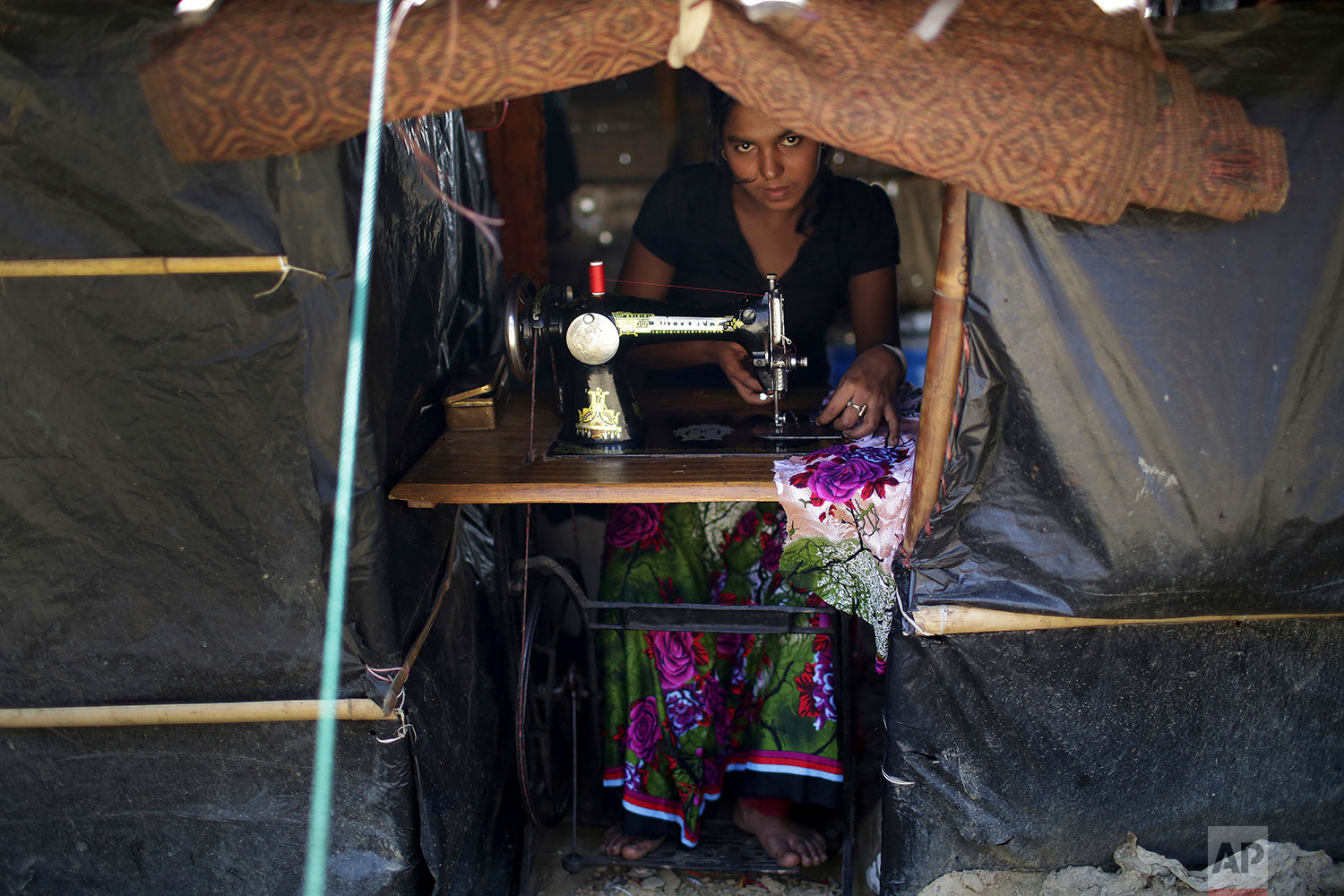A Rohingya Muslim woman works on her sewing machine inside her tent at Kutupalong refugee camp on Tuesday, Nov. 28, 2017, in Bangladesh. Since late August, more than 620,000 Rohingya have fled Myanmar's Rakhine state into neighboring Bangladesh, where they are living in squalid refugee camps. (AP Photo/Wong Maye-E)