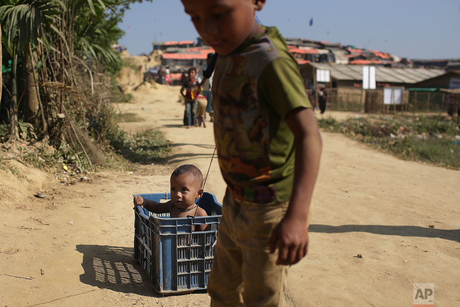 Rohingya Muslim children race make-shift carts made with plastic crates around Jamtoli refugee camp in Bangladesh on Monday, Nov. 27, 2017. Since late August, more than 620,000 Rohingya have fled Myanmar's Rakhine state into neighboring Bangladesh, where they are living in squalid refugee camps. (AP Photo/Wong Maye-E)