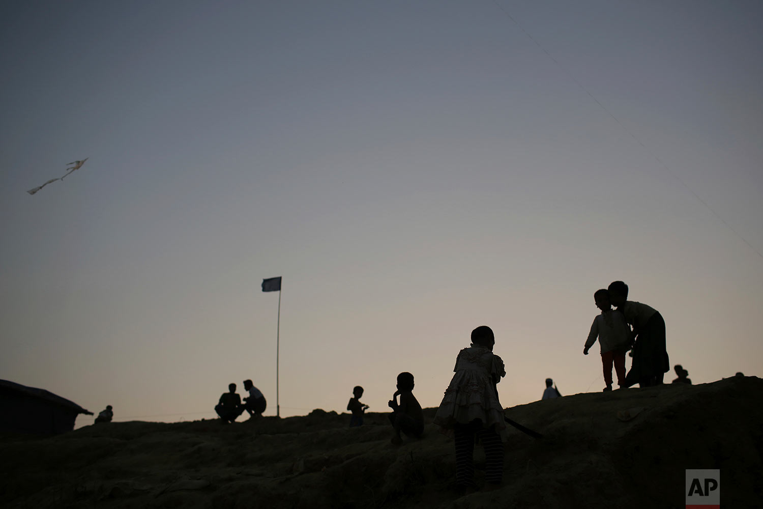 Rohingya Muslim children are silhouetted against the dusk sky in Jamtoli refugee camp on Monday, Nov. 27, 2017, in Bangladesh. Since late August, more than 620,000 Rohingya have fled Myanmar's Rakhine state into neighboring Bangladesh, where they are living in squalid refugee camps. (AP Photo/Wong Maye-E)