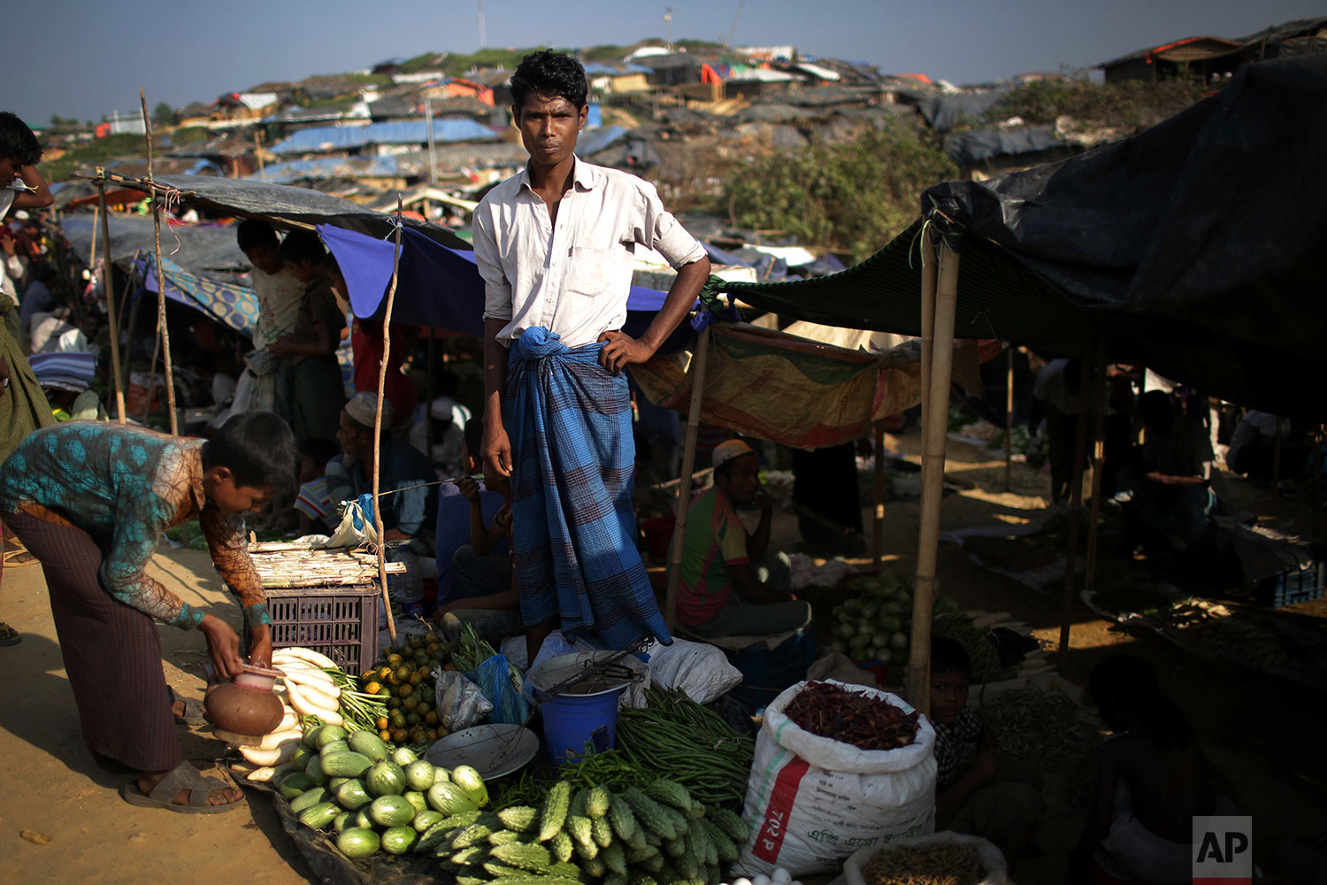 "A Rohingya Muslim man sells vegetables at a market on the outskirts of Kutupalong refugee camp, Bangladesh, Tuesday, Nov. 21, 2017. Since late August, more than 620,000 Rohingya have fled Myanmar's Rakhine state into neighboring Bangladesh, seeking safety from what the military described as ""clearance operations."" The United Nations and others have said the military's actions appeared to be a campaign of ""ethnic cleansing,"" using acts of violence and intimidation and burning down homes to force the Rohingya to leave their communities. (AP Photo/Wong Maye-E)"