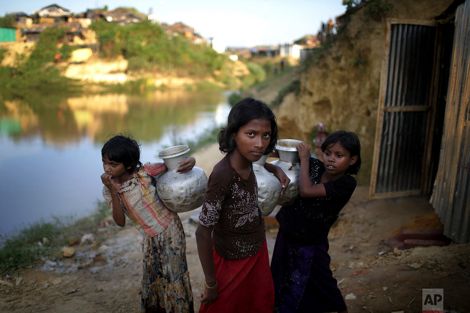 "In this Sunday, Nov. 19, 2017, photo, Rohingya Muslim girls carry water pots in Kutupalong refugee camp in Bangladesh.  More than 620,000 Rohingya have fled Rakhine for neighbouring Bangladesh since late August 2017, when the military launched what it called ""clearance operations"" in response to insurgent attacks. (AP Photo/Wong Maye-E)"